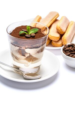 Classic tiramisu dessert in a glass cup, savoiardi cookies and coffee beans on white background Reklamní fotografie - 128694078