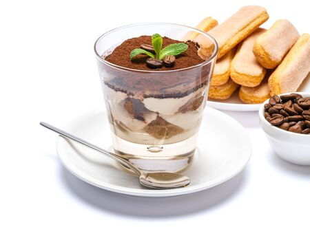 Classic tiramisu dessert in a glass cup, savoiardi cookies and coffee beans on white background Reklamní fotografie - 128694077