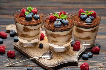 Classic tiramisu dessert with blueberries and strawberries in a glass cup on cutting board on wooden background Stockfoto