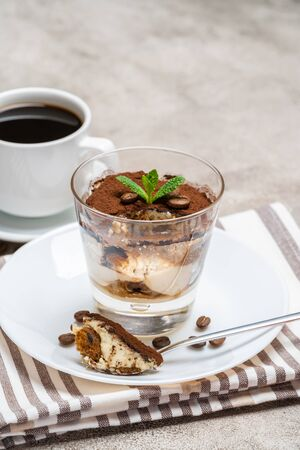 Portion of Classic tiramisu dessert in a glass and cup of coffee on concrete background