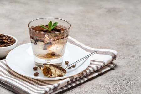 Portion of Classic tiramisu dessert in a glass cup on concrete background