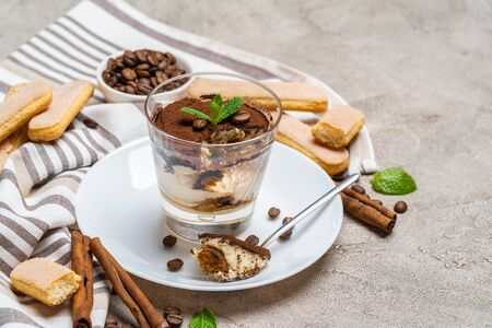 Portion of Classic tiramisu dessert in a glass, savoiardi cookies and cup of coffee on concrete background Stok Fotoğraf