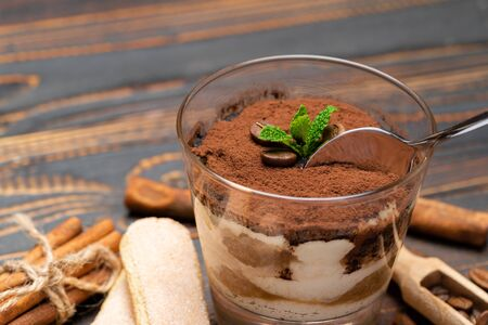 Portion of Classic tiramisu dessert in a glass and savoiardi cookies on wooden background
