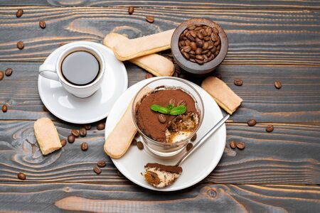 Portion of Classic tiramisu dessert in a glass, cup of coffee and savoiardi cookies on wooden background