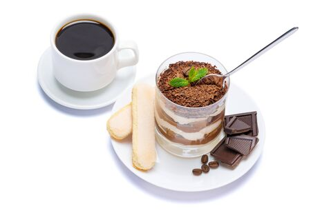 Classic tiramisu dessert in a glass, cup of coffee and pieces of chocolate on white background with clipping path