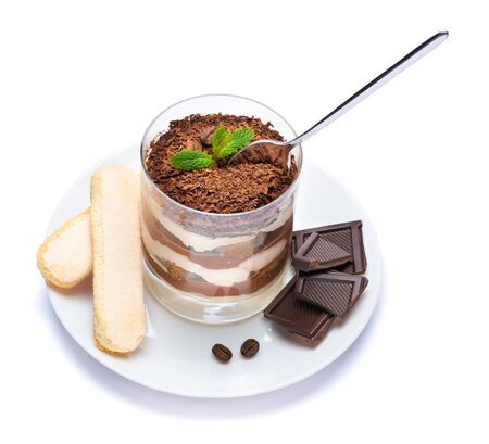 Classic tiramisu dessert in a glass cup on the plate and pieces of chocolate on white background with clipping path Stok Fotoğraf