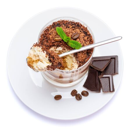 Classic tiramisu dessert in a glass cup on the plate and pieces of chocolate on white background with clipping path embedded