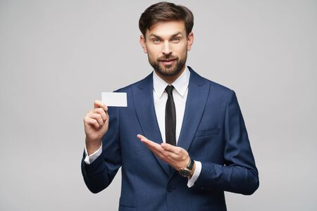 studio photo of young handsome businessman wearing suit holding business card Imagens