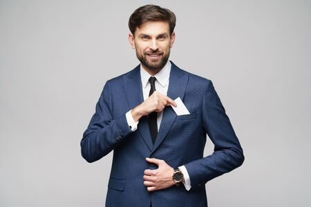 studio photo of young handsome businessman wearing suit holding business card