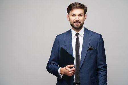 Porträt eines hübschen jungen Geschäftsmannes, der Ordner hält