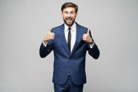 young business man going thumb up on grey background
