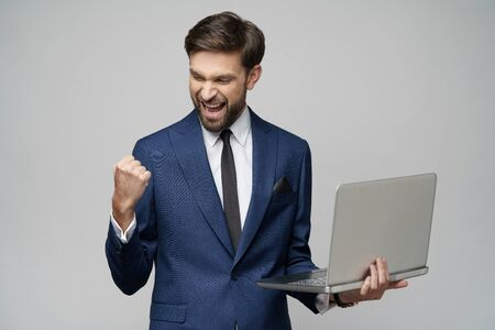 Young handsome businessman Holding a laptop Computer with Blank Screen