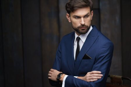 indoor photo of young handsome stylish businessman wearing suit Stockfoto