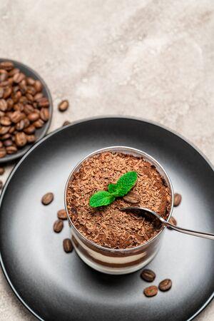 Classic tiramisu dessert in a glass cup on concrete background