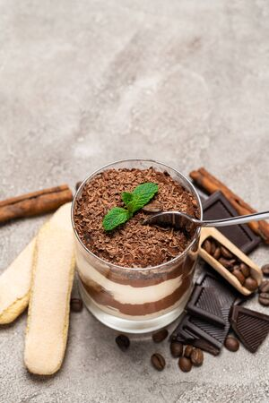 Classic tiramisu dessert in a glass cup, pieces of chocolate and savoiardi cookies on concrete background or table