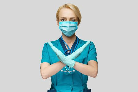 medical doctor nurse woman wearing protective mask and rubber or latex gloves - stop sign gesture