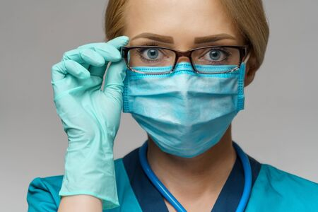 medical doctor nurse woman with stethoscope over light grey background - wearing protective mask and rubber or latex gloves. Banque d'images