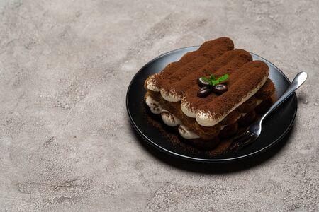 Classic tiramisu dessert on ceramic plate on light grey concrete background or table