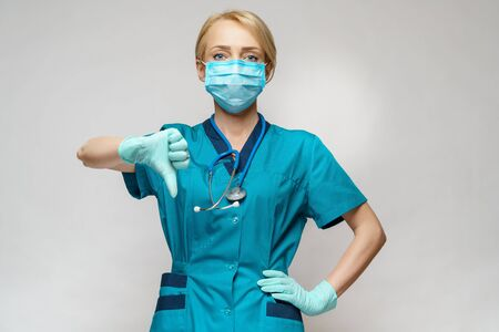 medical doctor nurse woman wearing protective mask and latex gloves - showing big thumb down