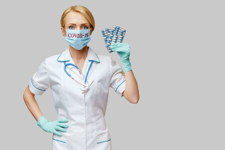 medical doctor nurse woman wearing protective mask and rubber or latex gloves - holding blisters of pills