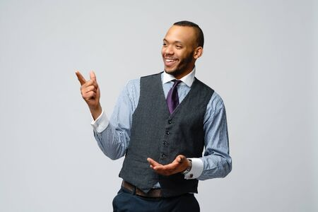 professional african-american business man - presenting points a hand at copy space