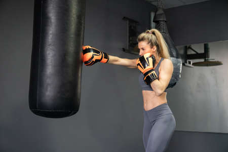 Young woman wearing punching gloves doing boxing training at the gym or fitness club Фото со стока