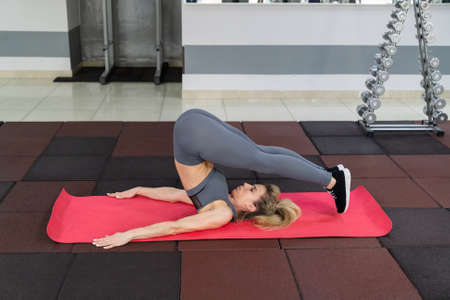 young woman stretching exercising indoors in fitness club