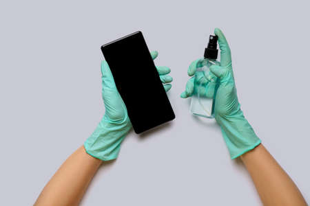 Females hands in latex gloves wiping mobile phone with alcohol decontaminating agent top view over light grey background