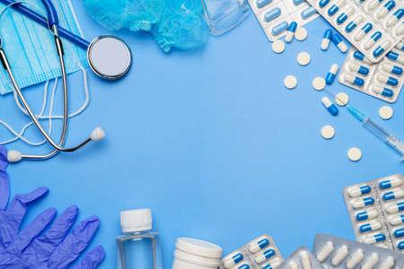 Coronavirus protection concept - stethoscope, protective mask, pills, syringe on blue background. Stock fotó