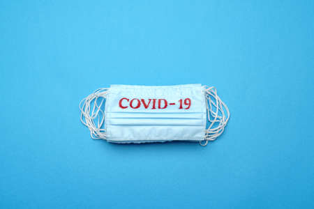 Stack of Disposable blue medical face masks with COVID-19 sign on blue background