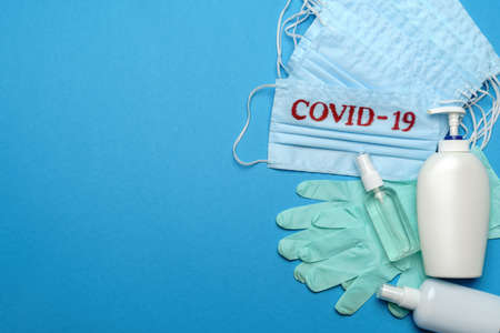 Stack of Disposable blue medical face masks with COVID-19 sign, rubber latex gloves and alcohol hand sanitizer antiseptic on blue background 写真素材