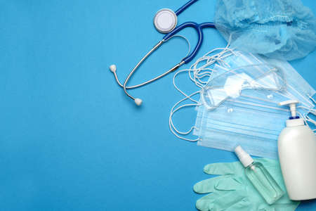 Stack of Disposable blue medical face masks, rubber latex gloves, goggles, stethoscope and alcohol hand sanitizer antiseptic on blue background