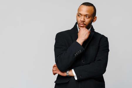 studio shot of a african-american businessman wearing coat over light grey background 写真素材