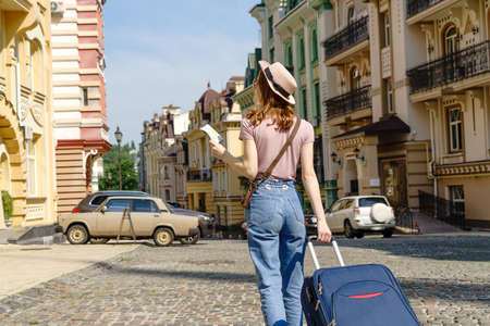 Beautiful Young Woman tourist Pleasant with city map and suitcase in the City Center