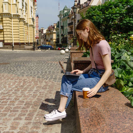 Beautiful Young Woman tourist with takeout coffee in the City Center using laptop