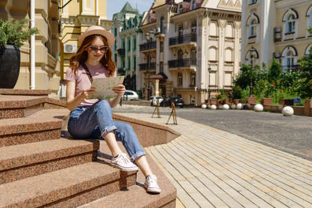 Beautiful Young Woman tourist Pleasant with city map sitting on stairs in the City Center