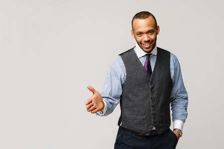handsome african-american businessman handshake gesture over light grey background 版權商用圖片