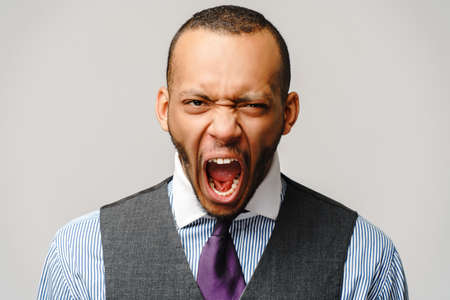 Angry african-american businessman in stress over light grey background