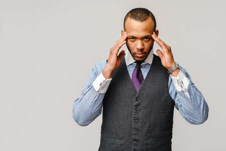 Young afro american businessman touching head because of headache and stress