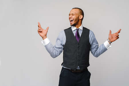 young funny african-american businessman crossing fingers, wishing, hoping for best, miracle over grey background