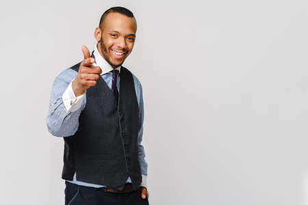 Handsome American-African man pointing you while standing against grey background. 版權商用圖片