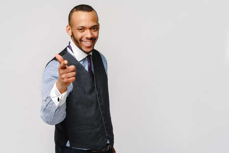 Handsome American-African man pointing you while standing against grey background