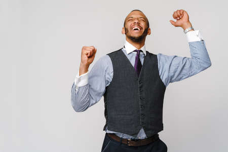 Young smart shouting african-american businessman doing success win gesture