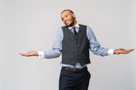 Doubt concept - Young african american businessman wearing tie and over light grey background clueless and confused expression with arms and hands raised 스톡 콘텐츠