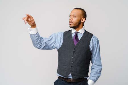Handsome young african american businessman pointing his finger to virtual screen image or text 版權商用圖片