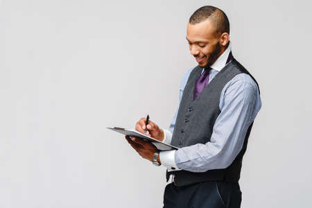 a young african american man holding plain table tablet and pen