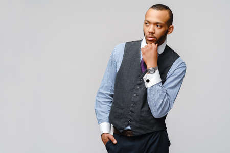Studio shot of young African-American businessmanman over grey background 版權商用圖片