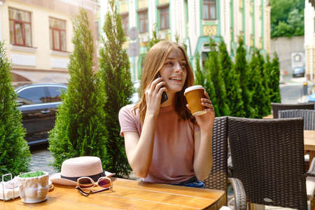 young woman talking on the phone in a cafe on a summer terrace