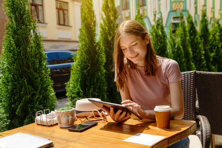 young woman using tablet pc in a cafe on a summer terrace