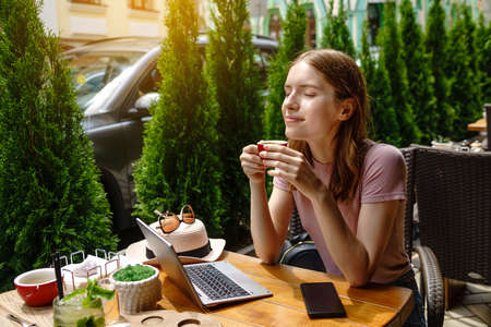 young woman using laptop in a cafe on a summer terrace